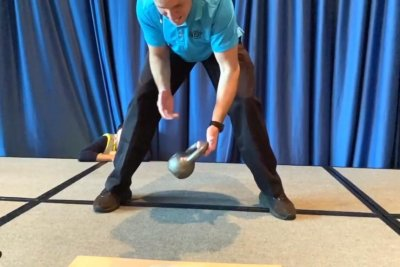 Man passes 20-pound weight from hand to hand 100 times in 15 seconds