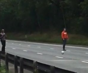 Commuters stranded on highway play soccer in the road