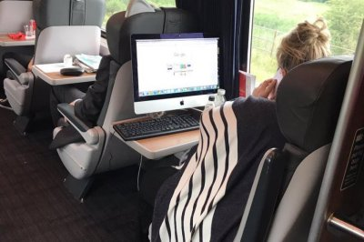 Train passenger sets up desktop computer on seat tray