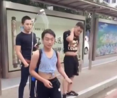 Man uses portable shower backpack to keep cool at bus stop