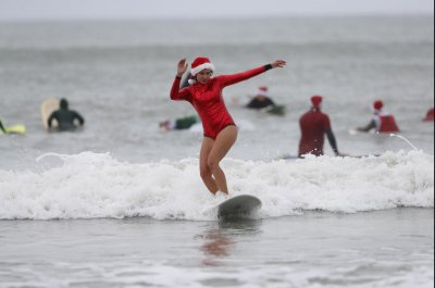 Nearly 600 'Surfing Santas' take to the waves in Florida