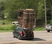 Small car transports huge load of wooden pallets