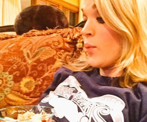 Carrie Underwood uses baby bump as table in new photo