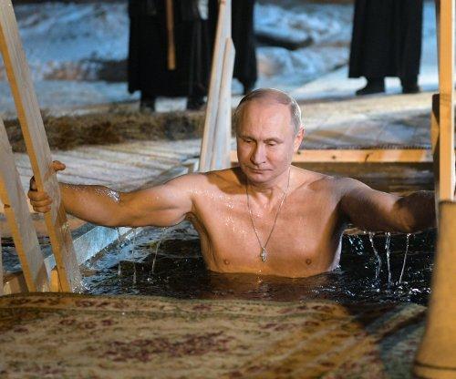 Putin takes icy plunge into lake for Epiphany celebration