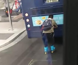 Inline skater hitches a ride on the back of Irish bus