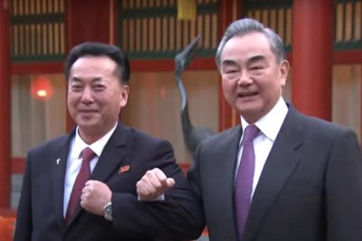 China, North Korea envoys lock arms in first official meeting