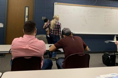 Professor carries student's baby during lecture