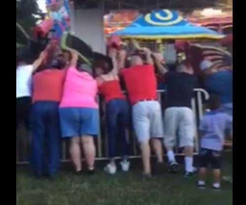 Bystanders prop up collapsing roller coaster with kids on board at Georgia fair