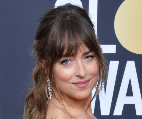Report: Dakota Johnson, Chris Martin get close at fashion event