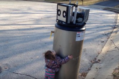 Little girl makes friends with water heater 'robot'