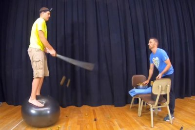 Man uses sword to slice 62 kiwis while standing on inflatable ball