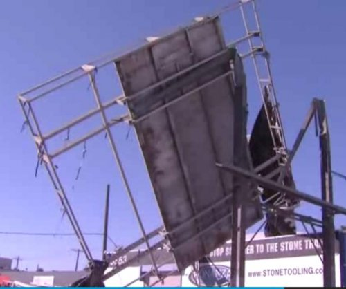 Wind topples billboard, pickup truck narrowly evades disaster