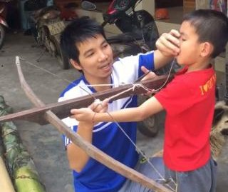 Dad helps son remove loose tooth with crossbow