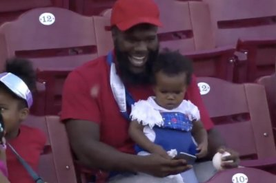 Reds fan makes incredible catch while holding baby