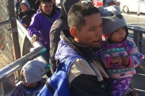 Cold weather drives migrants camped at border bridge into shelter