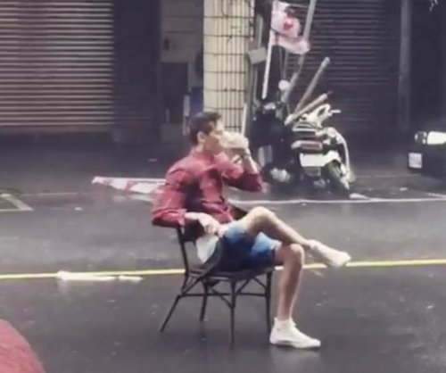 Men attempt to continue daily routine during Taiwan typhoon