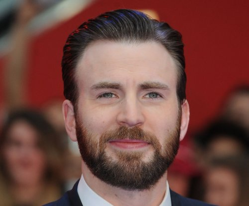 Chris Evans gets a little help from his dog while taking part in The 22 Push-up Challenge