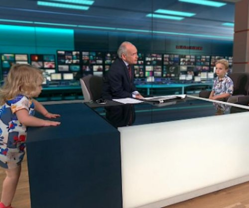 Toddler climbs around set of live ITV interview