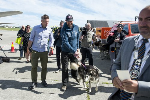 Sled dog race champion, 24 dogs, land after historic plane ride home