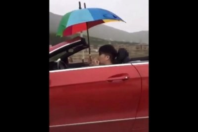 Man holds umbrella while driving convertible in the rain