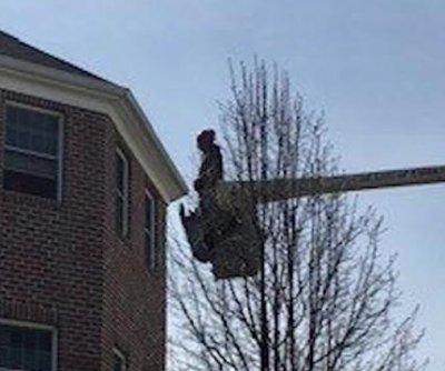 Man uses bucket truck to visit mom's third floor window
