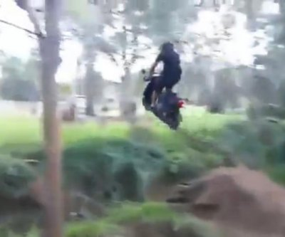 Australian jumps creek on small engine motor scooter