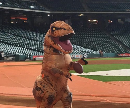 Houston Astros players toss football while wearing T-Rex costume
