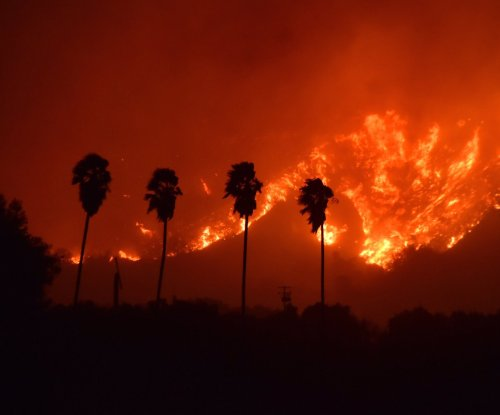 1 dead as 27,000 evacuate wildfires in Southern California