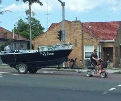 Man uses mobility scooter to tow large boat down road