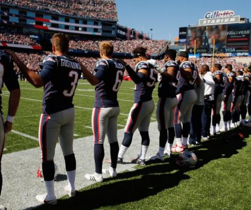 New England Patriots, Carolina Panthers stand during national anthem