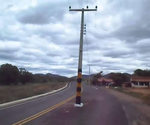 Traveler perplexed by telephone pole sticking up from road