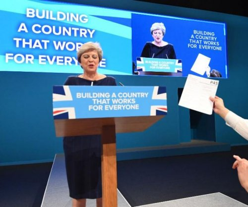 British PM May given unemployment form by a heckler during speech