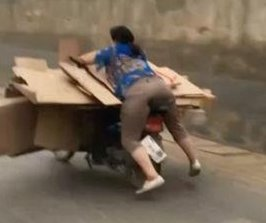 Load of boxes leaves woman hanging off back of scooter