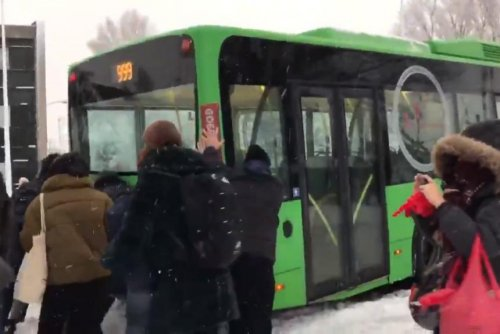 Passengers and bystanders free bus stuck in the snow