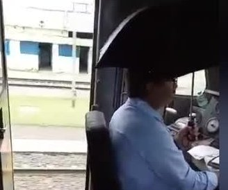 Leaky train driver stays dry using umbrella in India