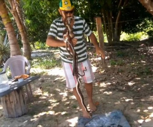 Rainforest activist walks on broken glass with four snakes in his mouth