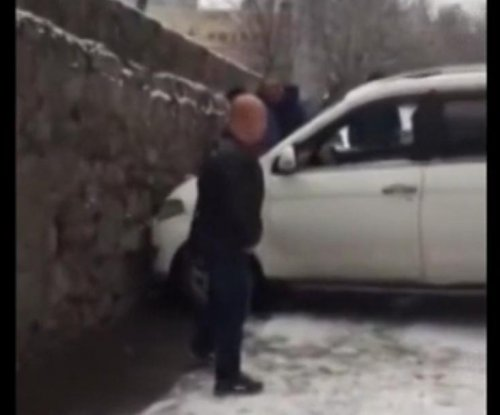 Car slips on snowy road, gets wedged between two walls