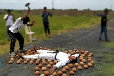 Blindfolded man smashes 50 coconuts around another man's body