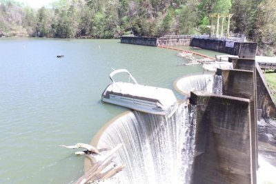 Wind leaves pontoon boat perched at edge of dam
