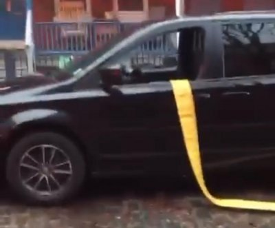 Firefighters run hose through vehicle parked next to hydrant