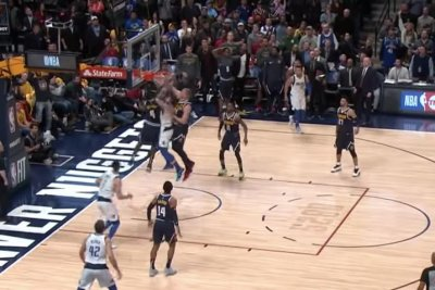Mavericks' Luka Doncic dunks between two Nuggets defenders