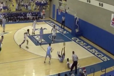 Baruch College senior swishes deep shot while sitting on court