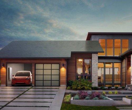 Tesla unveils sleek glass solar roof tiles