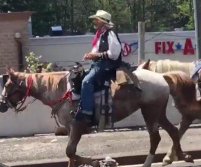 Cowboy with two horses blocks traffic on New York bridge