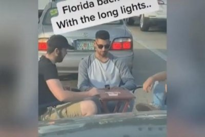Friends play Uno in the road during long red light