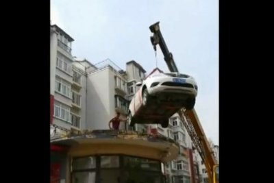 Crane lifts illegally parked car onto roof of building