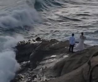Giant wave sweeps newlyweds into the ocean during photo shoot