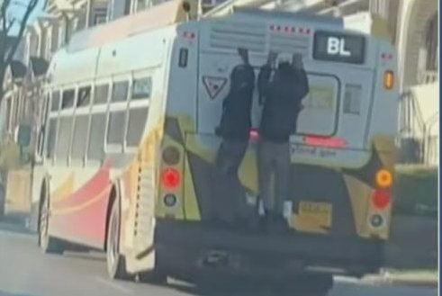 Men caught on camera hitching a ride on back of Baltimore bus