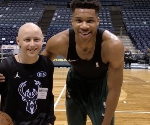 Bucks' Giannis Antetokounmpo warms up with boy with bone cancer