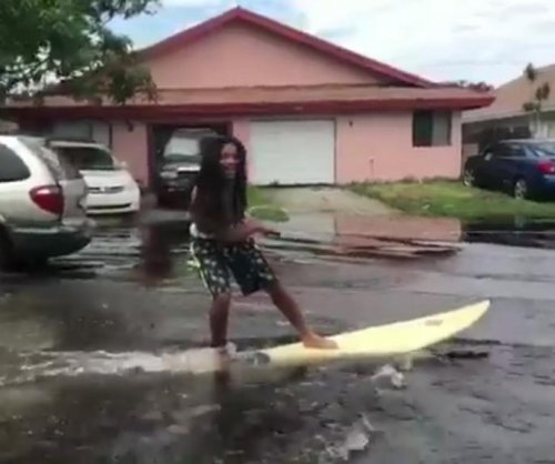 Florida men cruise flooded street on surfboard